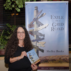 Shelley Banks, with Exile on a Grid Road book and banner.